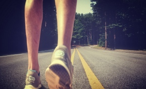 Feet of an athlete running on a deserted road - Training for fit